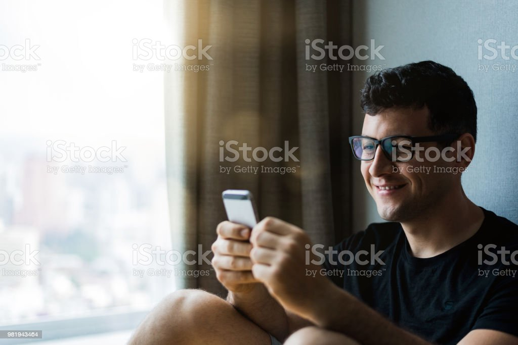Happy Young Man Looking At Mobile