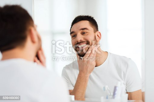 istock happy young man looking to mirror at home bathroom 539469392