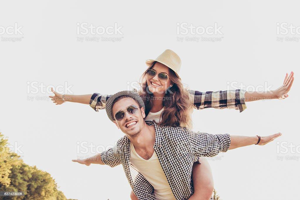 Happy young man piggybacking his girlfriend. stock photo