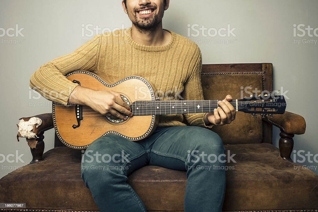 Happy young man playing guitar on old sofa royalty-free stock photo