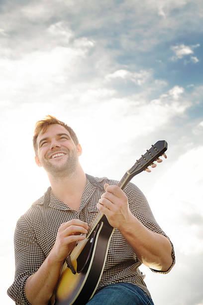 Feliz jovem tocando o mandoline ao ar livre - foto de acervo