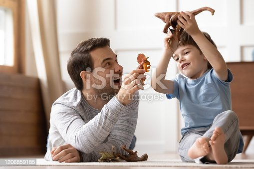 Full length happy young man dad lying on heated warm floor, playing toys with joyful small schoolboy son at home. Overjoyed two generations family enjoying weekend playtime together in living room.