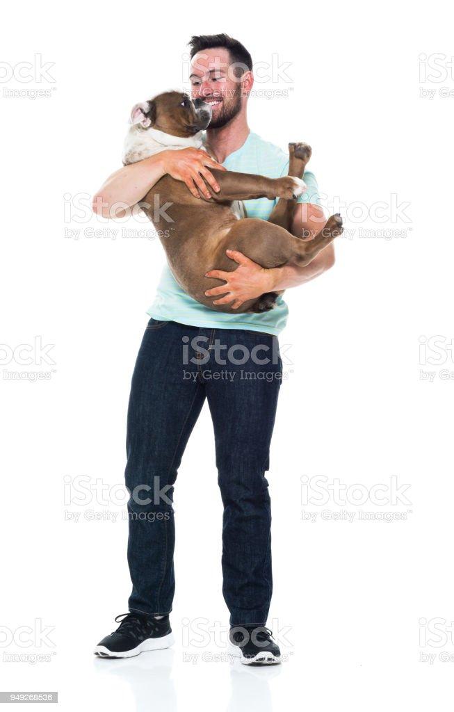 Glücklicher junge Mann spielt mit seinem bulldog – Foto