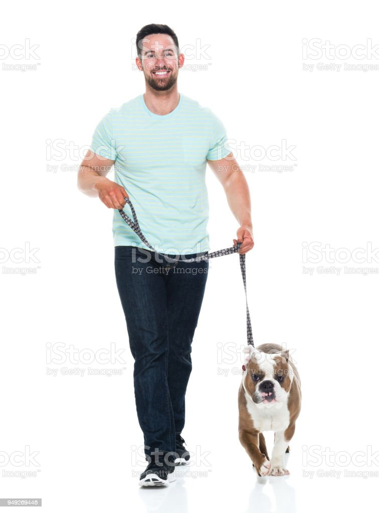 Happy young man playing with his bulldog stock photo
