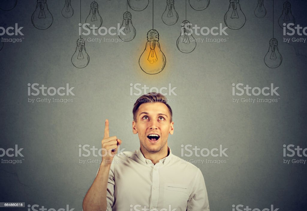 happy young man pointing at light bulb has a solution – zdjęcie