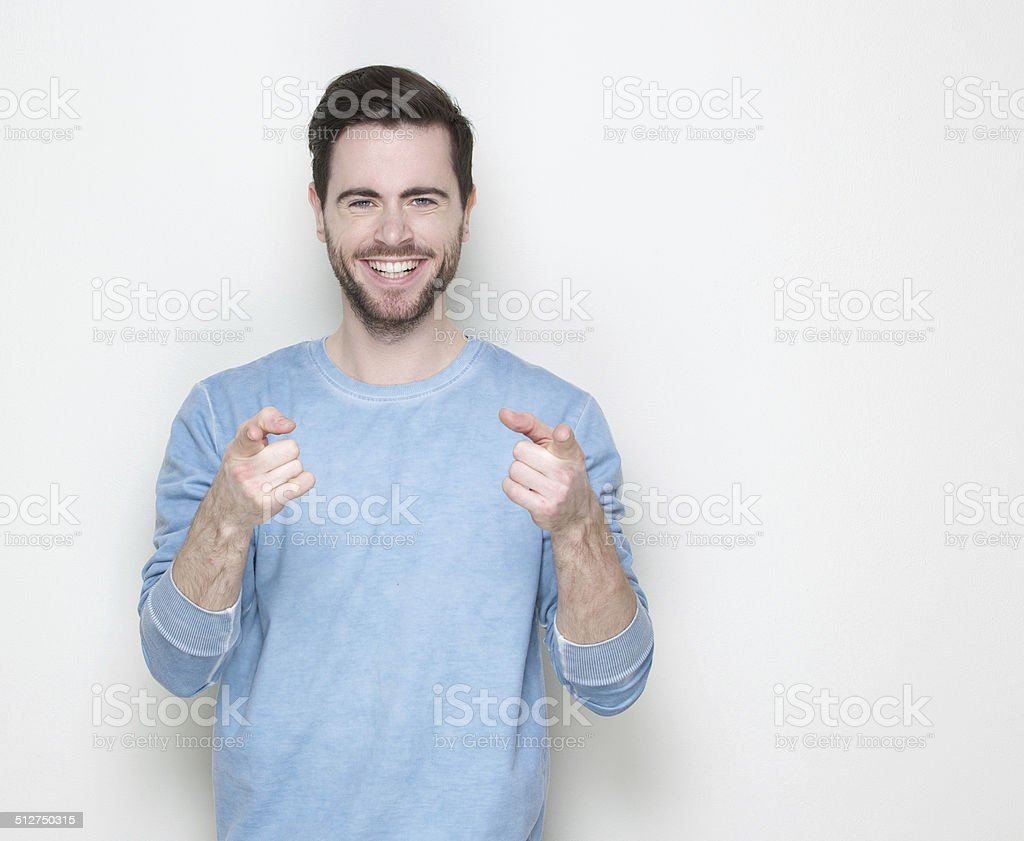 Happy young man pointing fingers stock photo