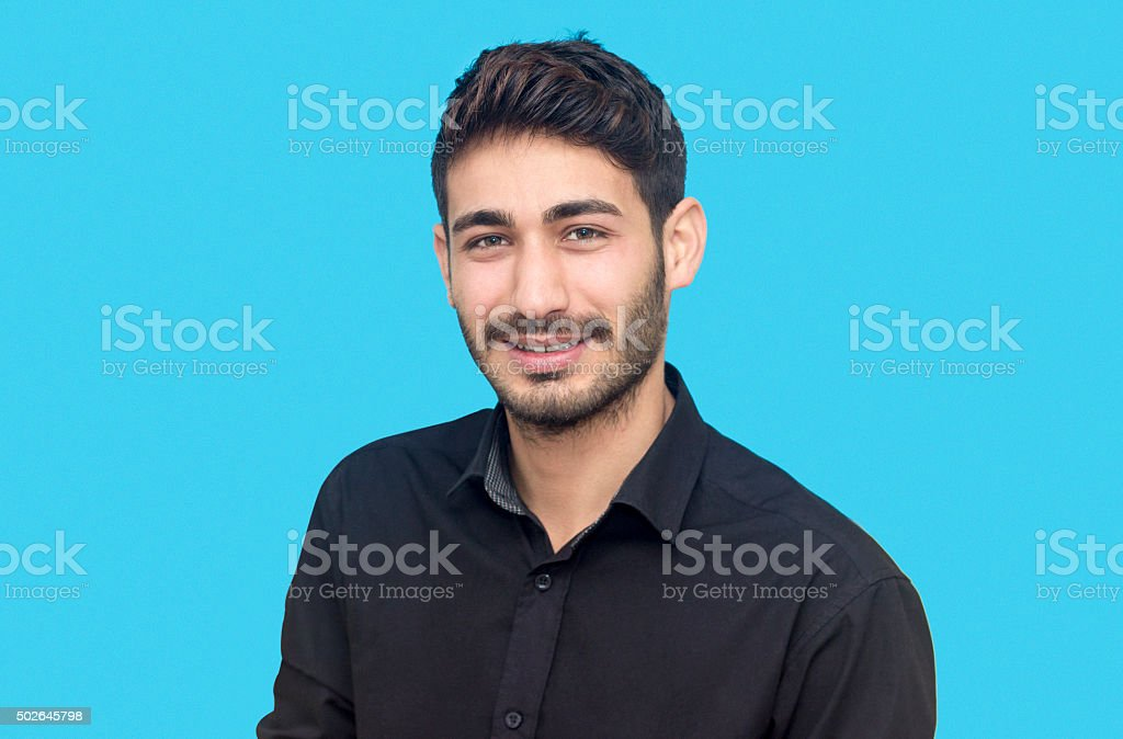 Happy young man portrait against blue background stock photo