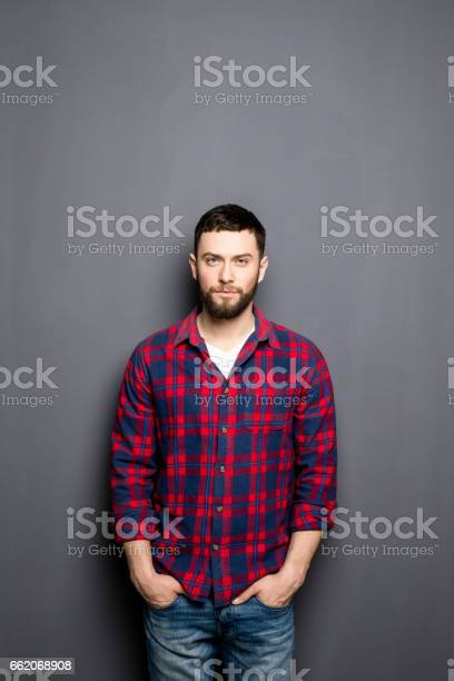 Happy young man. Portrait of handsome young man in casual shirt with hands in pockets and smiling while standing against grey background