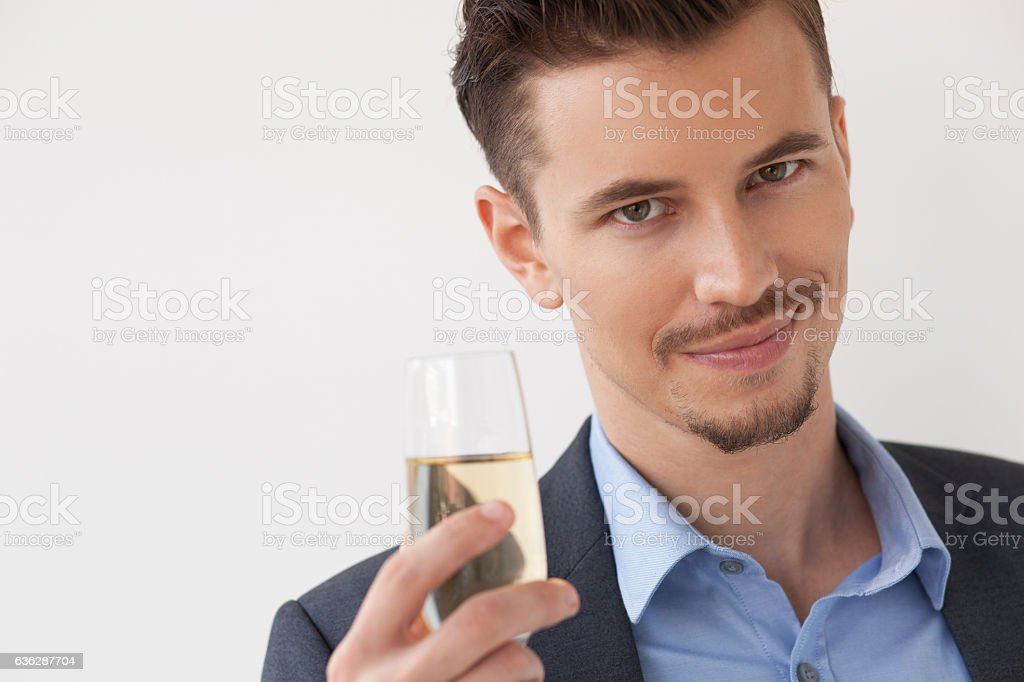 Happy young man raising champagne flute stock photo