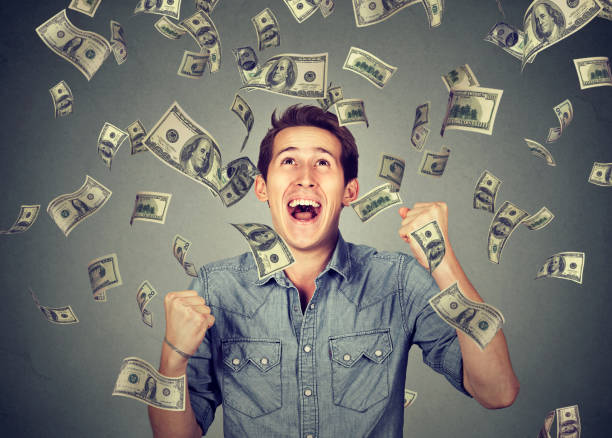 Happy young man screaming super excited Happy young man screaming super excited. Portrait ecstatic guy celebrates success under money rain falling down dollar bills banknotes isolated gray background. Financial freedom concept lottery stock pictures, royalty-free photos & images