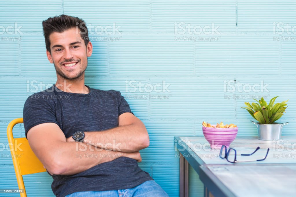 Happy young man seating in a restaurant stock photo