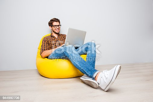 istock Happy young man sitting in yellow pouf  and using laptop 944992706