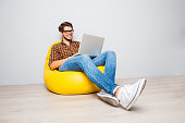 Happy young man sitting in yellow pouf  and using laptop