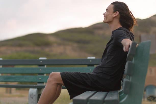 buon giovanotto seduto su una panchina fuori, sentendosi bene. - assuefazione foto e immagini stock