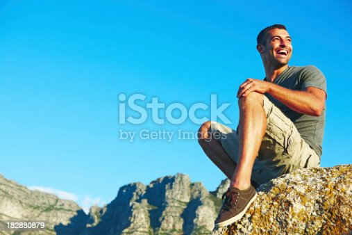 Low angle view of an adventurous young guy looking away against blue sky