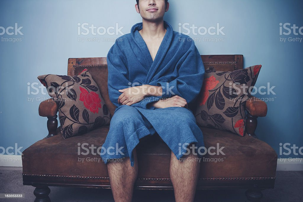 Happy young man sitting on sofa royalty-free stock photo