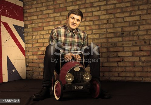 496487362istockphoto Happy Young Man Sitting on Vintage Toy Car 478824348