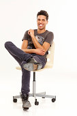 istock Happy young man sitting relaxed on chair 181089881