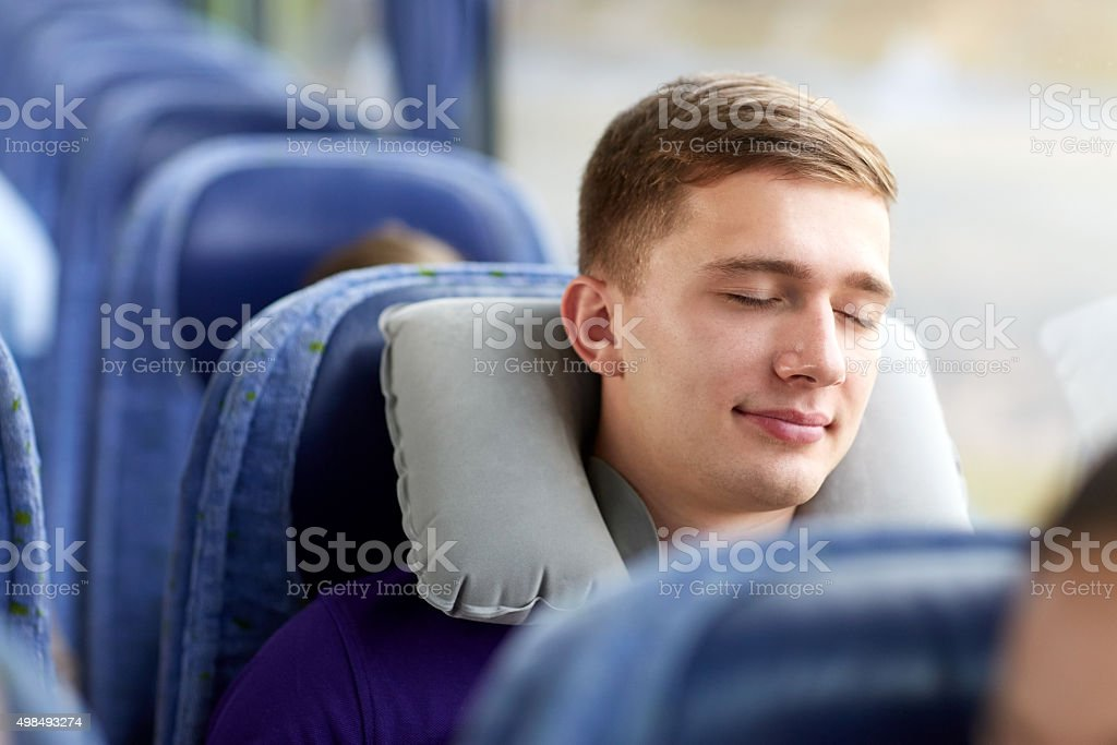 happy young man sleeping in travel bus with pillow stock photo