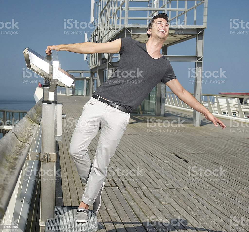 Happy young man standing on pier with joy royalty-free stock photo