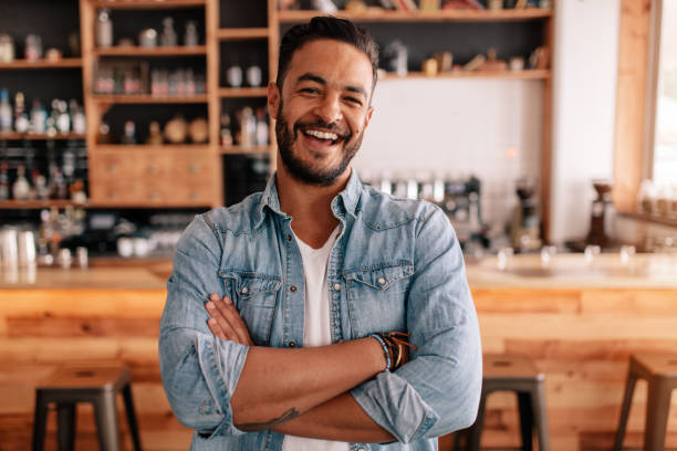 Happy young man standing with his arms crossed in a cafe stock photo