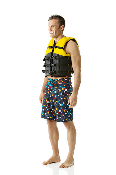 Happy young man standing with life jacket stock photo