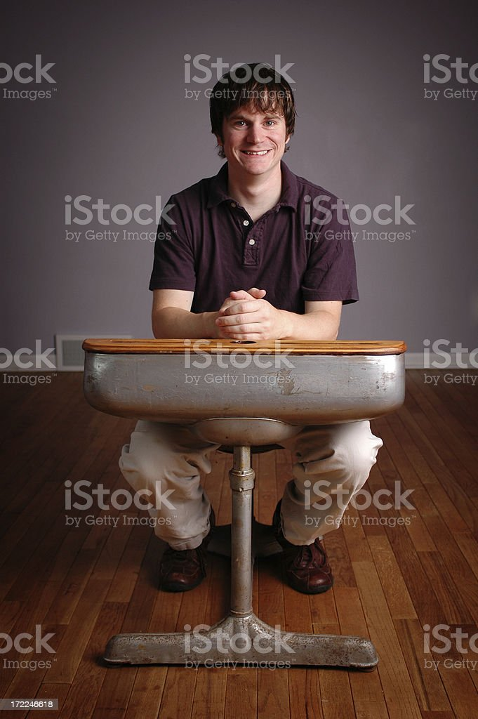 Happy Young Man Student Sitting in Old School Desk royalty-free stock photo