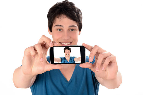 Happy young man taking a selfie photo with his smartphone. stock photo