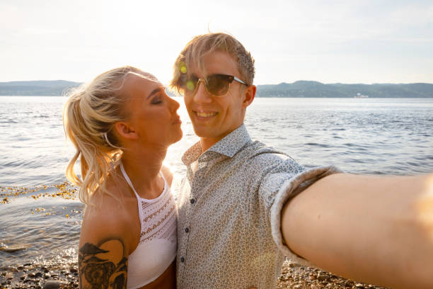 Happy Young Man Taking Selfie With Girlfriend At Beach stock photo