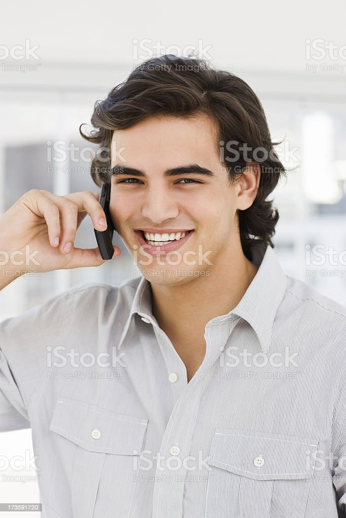 Happy young man talking on mobile phone royalty-free stock photo