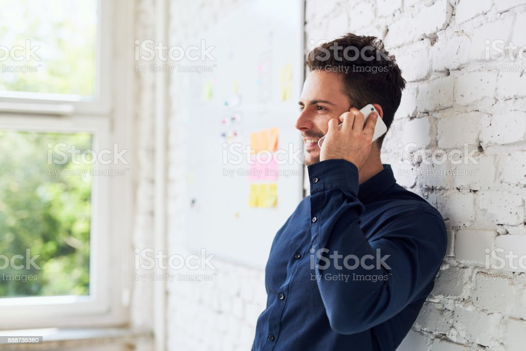 Happy young man talking on the phone at modern office stock photo