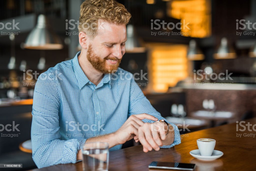 Happy young man using a smart watch while sitting in coffee shop.
