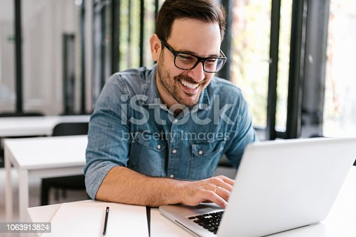 Happy young man using laptop. Close-up.