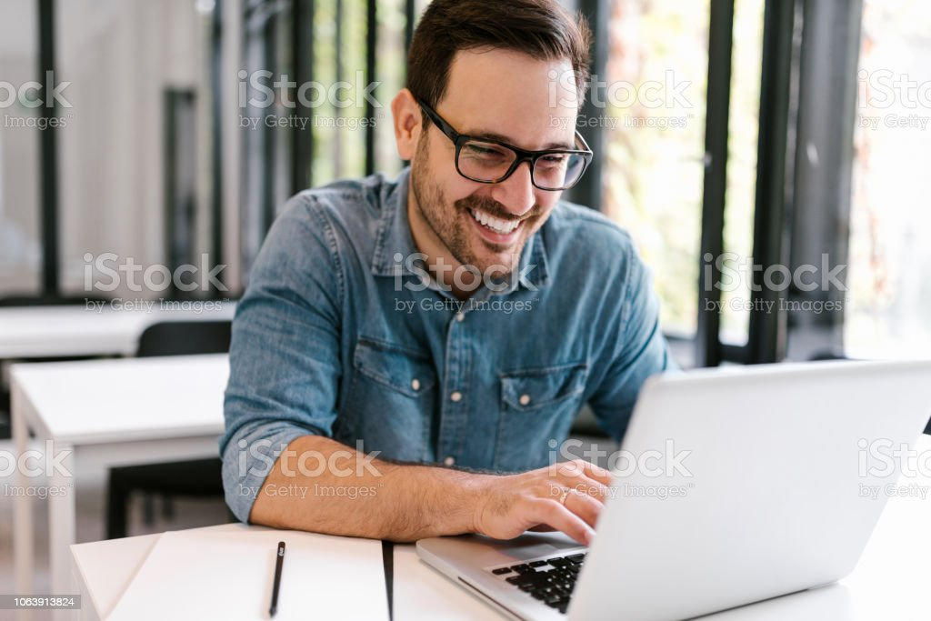 Happy young man using laptop. Close-up. stock photo