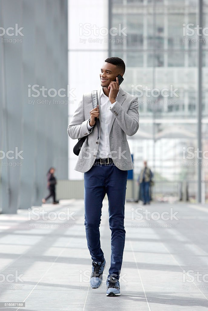 Happy young man walking and talking on mobile phone stock photo