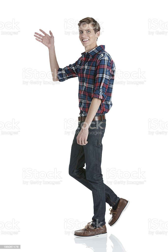 Happy young man waving his hand stock photo