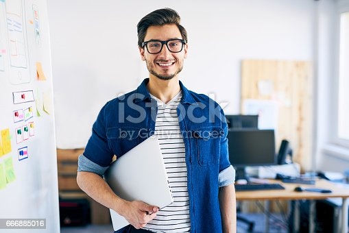 istock Happy young man, web designer standing with laptop 666885016