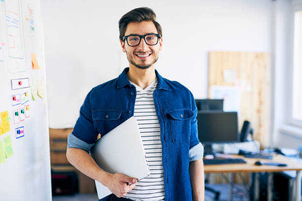 Happy young man, web designer standing with laptop Happy young man, web designer standing with laptop nerd stock pictures, royalty-free photos & images