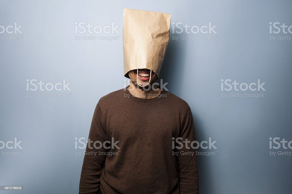 Happy young man with a bag over his head stock photo