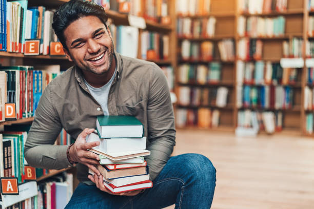 Happy young man with a pile of books in a bookstore stock photo