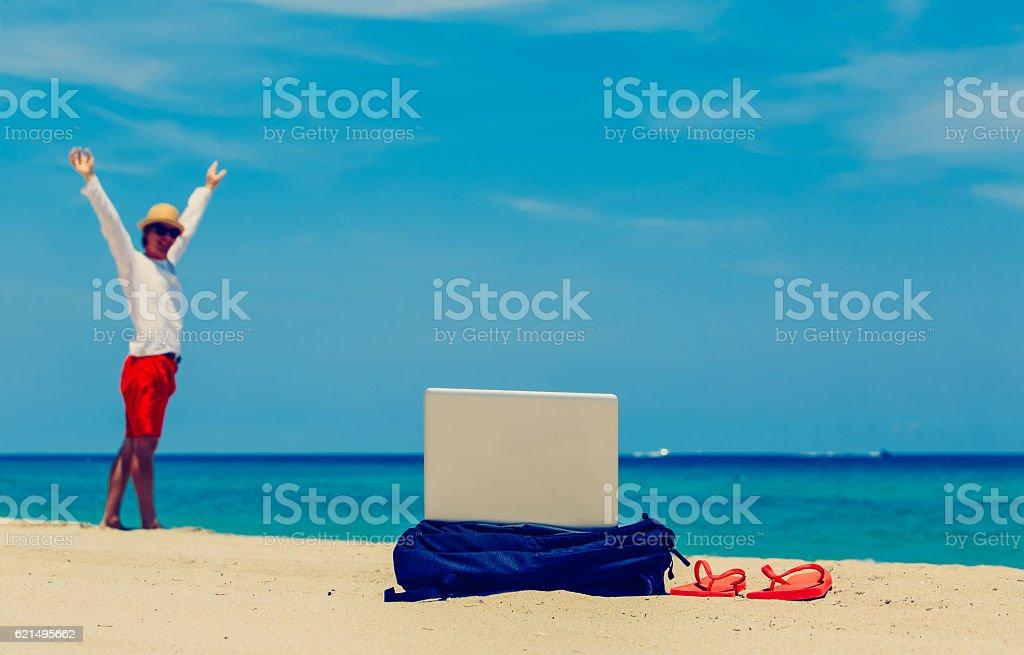 Heureux jeune homme avec sac à dos et ordinateur portable sur la plage photo libre de droits