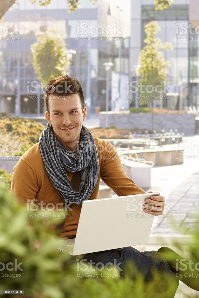 Happy young man with laptop outdoors royalty-free stock photo