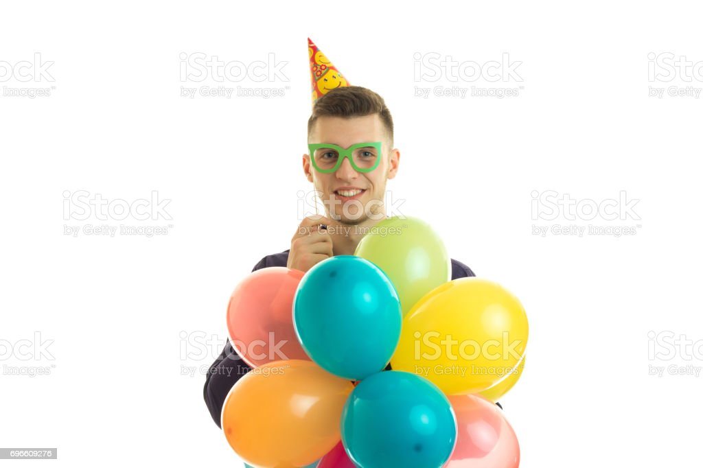 Happy young man with paper glasses and balloons in hands smiling on camera stock photo
