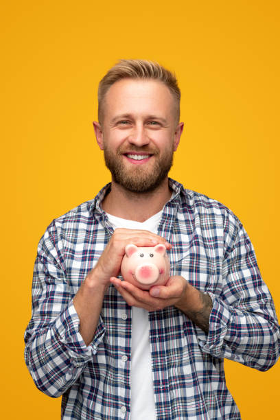 Happy young man with piggy bank stock photo