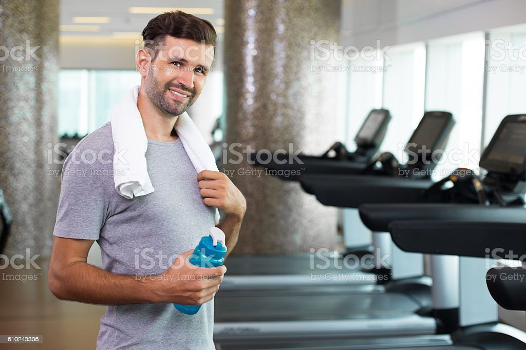 Happy young man with water bottle standing in gym stock photo