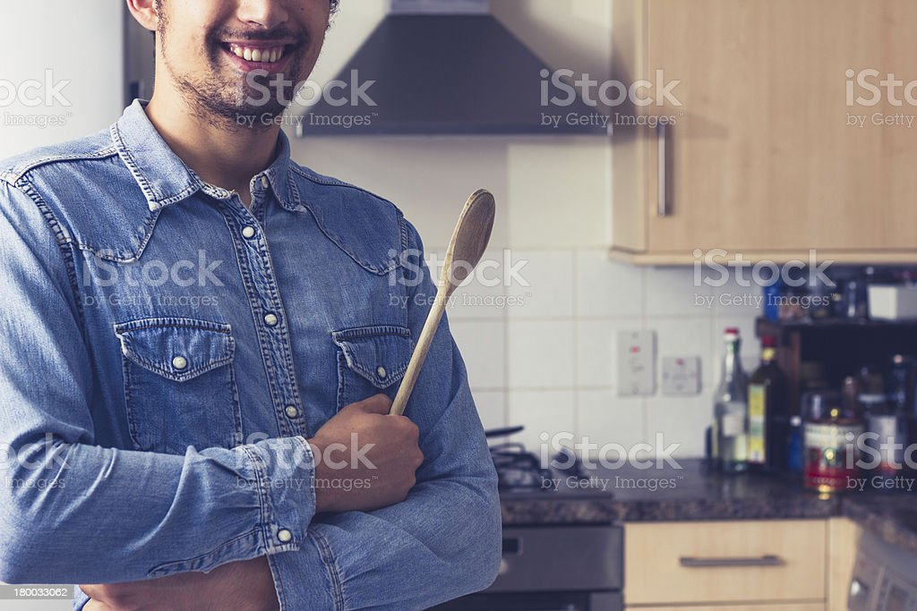Happy young man with wooden spoon in kitchen royalty-free stock photo