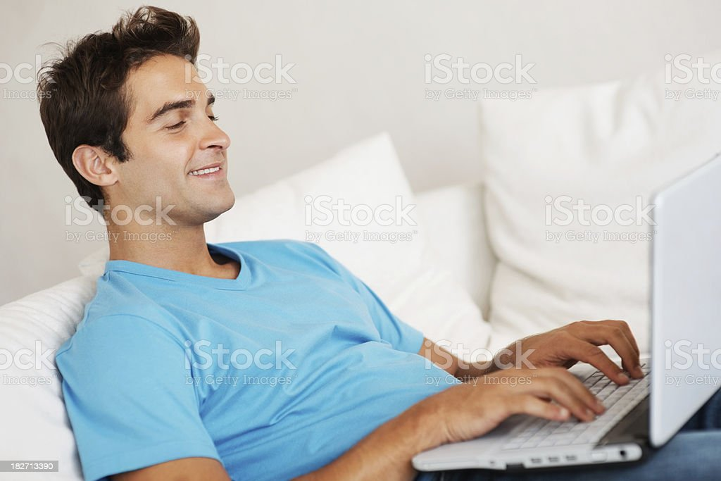 Happy young man working on a laptop royalty-free stock photo