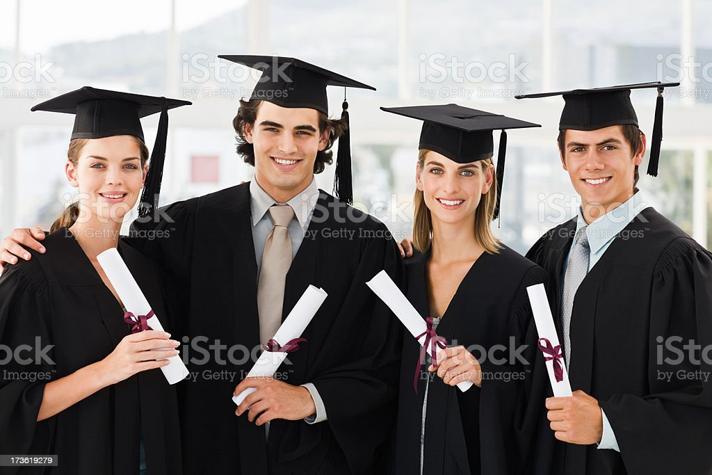 Happy young men and women holding graduation certificates royalty-free stock photo