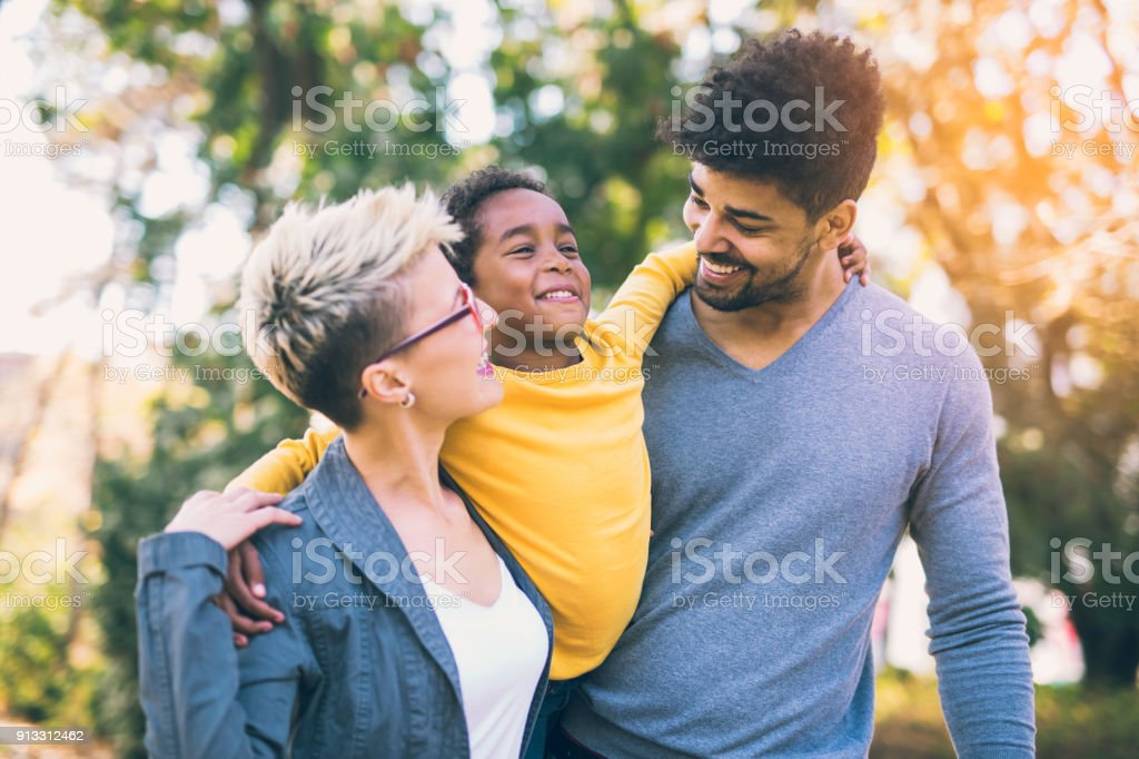 Happy young mixed race couple spending time with their daughter stock photo