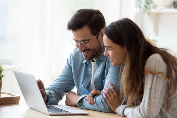 Happy young mixed race couple watching funny videos on computer. stock photo